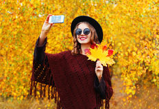 Autumn fashion smiling young woman taking picture makes self portrait on smartphone over sunny yellow leaves Stock Photography