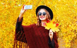Autumn fashion smiling young woman taking a picture self portrait. On the smartphone in knitted poncho Stock Photography