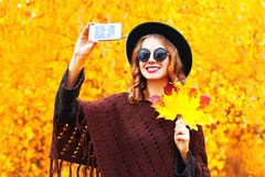 Autumn fashion smiling young woman taking a picture self portrait on the smartphone. Wearing a knitted poncho Stock Photography
