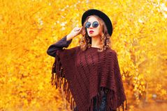 Autumn fashion woman wearing a black round hat, knitted poncho. On a yellow leaves background royalty free stock image
