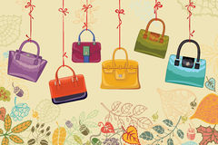 Autumn fashion. Women's handbags and leaves border. Colorful fashion women handbags hang on a ribbon stock illustration
