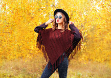 Autumn fashion young woman model wearing a black hat sunglasses and knitted poncho over yellow leaves Stock Photos