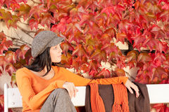 Autumn fashion young woman relax on bench. Autumn leaves park scenery young woman relax sitting on bench stock photography