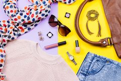Autumn female clothing - pink sweater, blue jeans, leather handbag, printed scarf, accessories and make up products. Top view Royalty Free Stock Photography