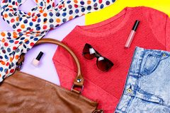 Autumn female clothing - red sweater, blue jeans, leather handbag, printed scarf, accessories and make up products. Top view Stock Image
