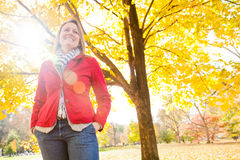 Autumn Flare. An attractive woman wearing a red coat highlighted by a lens flare on a fall day. The image orientation is horizontal and has copy space Royalty Free Stock Photography