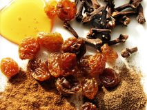 Autumn Flavors. Array of golden raisins, honey, cloves, cinnamon, and allspice Stock Photo