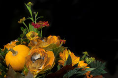 Autumn floral composition. Floral composition with flowers and pumpkin on the black backround Stock Images