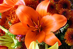 Autumn Flowers. Orange and yellow lillies, chrysanthemums, foliage and berries stock photo