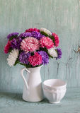 Autumn flowers asters in a white enamel jug and white ceramic bowl on a light wooden surface. Stock Image