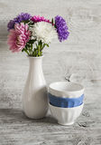 Autumn flowers asters in a white vase and ceramic bowl on a light wooden surface Stock Image