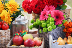Autumn flowers in a basket, apples and pears Stock Images