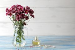 Autumn flowers of chrysanthemum in a jug and perfume on a blue wooden table royalty free stock image