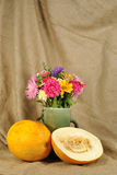 The autumn flowers and orange melon Stock Photo