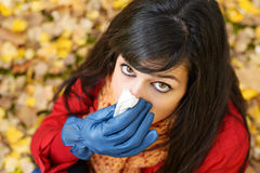 Autumn flu and cold. Sad woman with flu blowing her nose with a kleenex on a cold autumn day. Autumn golden leaves on ground Stock Photos