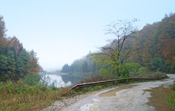Autumn fog on the lake and old, mountain road Royalty Free Stock Images