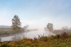 Autumn foggy morning. Dawn on the misty calm river Stock Photos