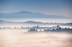Autumn foggy morning in mountains. Alpine village on the hills Stock Photography