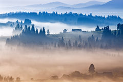Autumn foggy sunrise in mountains. Alpine village on September h Royalty Free Stock Image