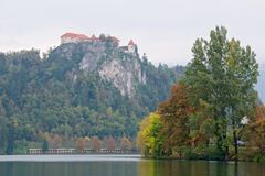 Autumn foliage around Bled Lake with Bled Castle on the precipice in Slovenia Royalty Free Stock Photography