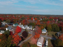 AUTUMN FOLIAGE IN  BRIGHT COLORS IN MAINE. HOMES IN A TOWN IN MAINE ON A FALL DAY WITH A BLUE SKY, CLOUDS, AND TREES WITH BRIGHT RED, ORANGE, AND GREEN LEAVES Stock Photos