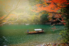 Autumn foliage at Hozu river, Arashiyama. ARASHIYAMA, KYOTO, JAPAN - NOVEMBER 23, 2016: Unidentified people on wooden boat at Hozu River to enjoy autumn maple Stock Photo