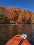 Autumn foliage with kayak in the foreground. Colorful Fall leave. Beautiful Canadian Fall folliage in New Brunswick. Kayaking on the Saint John River in the Fall royalty free stock image