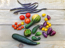Autumn food background. Beans, tomatoes, peppers, zucchini, cucumber on light wooden surface. Top view Stock Images
