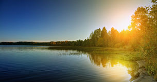 Autumn forest on the bank of the river. Sunset over the lake in the autumn forest Stock Photo
