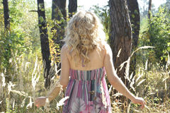 In the autumn forest on a glade curly girl in tall grass in the Stock Photography