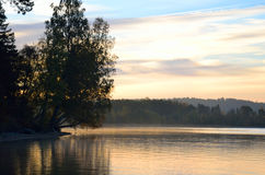 Autumn forest on the lake at sunrise. Stock Image