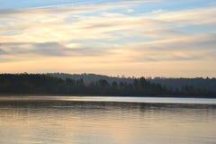 Autumn forest on the lake at sunrise. Stock Photo