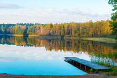 Autumn forest and lake. View with wooden footbridge Royalty Free Stock Images