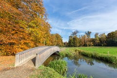 Autumn forest landscape with wooden bridge over water Stock Photography