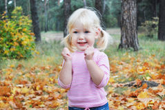 In the autumn forest little blonde girl enthusiastically shouts Royalty Free Stock Photos