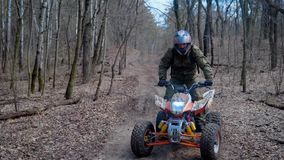 Autumn forest. The man in a special form on the ATV. The racer rides on the wood the racing ATV. stock video footage