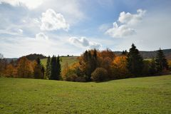 Autumn Forest in Mountain 1. Mountain Autumn Landscape with Colorful Forest and Green Field Royalty Free Stock Photography