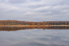 Autumn forest reflected in lake Stock Images