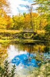Autumn forest reflection landscape. Forest, pond, & foot bridge royalty free stock photo