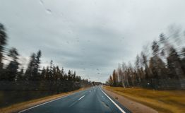 Autumn forest road at high speed drive. View from windscreen with drops Stock Photo