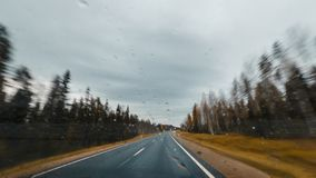 Autumn forest road at high speed drive. View from windscreen with drops Stock Photos