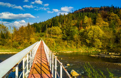 Autumn forest and sky and mountains and bridge over river. Autumn forest and blue sky and mountains and bridge over river Royalty Free Stock Images