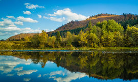 Autumn forest and sky and mountains and river. Autumn forest and blue sky and mountains and river Royalty Free Stock Images