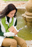 Autumn fountain young woman read book Royalty Free Stock Photography