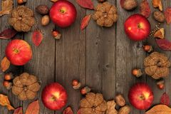 Autumn frame of apples, leaves, nuts and decor on wood Stock Images