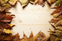 Autumn frame. Autumnal frame made ​​of fallen leaves and a wooden board Stock Photo