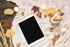 Autumn frame made of dried fall leaves, mug of cocoa with marshmellows, nuts, cinnamon, plaid, apples with tablet mock up Royalty Free Stock Photos