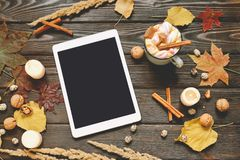 Autumn frame made of dried fall leaves, mug of cocoa with marshmellows, nuts, cinnamon, plaid, apples with tablet mock up. Top view on brown wood background royalty free stock photos