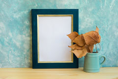 Autumn frame mockup, blue and golden border, tree branch with dry leaves in pitches, bluish concrete wall background, rustic. Minimalist nordic style, fall mood stock photos