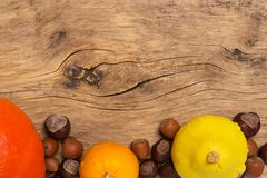 Autumn frame on old wooden background with pumpkins and nuts Royalty Free Stock Photo